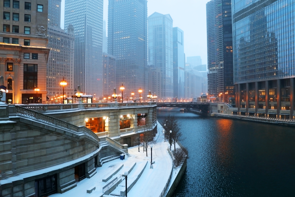 A foggy day winter day in Chicago. There is snow on the ground, the street lights are on, and you can see the Chicago River which looks frozen.