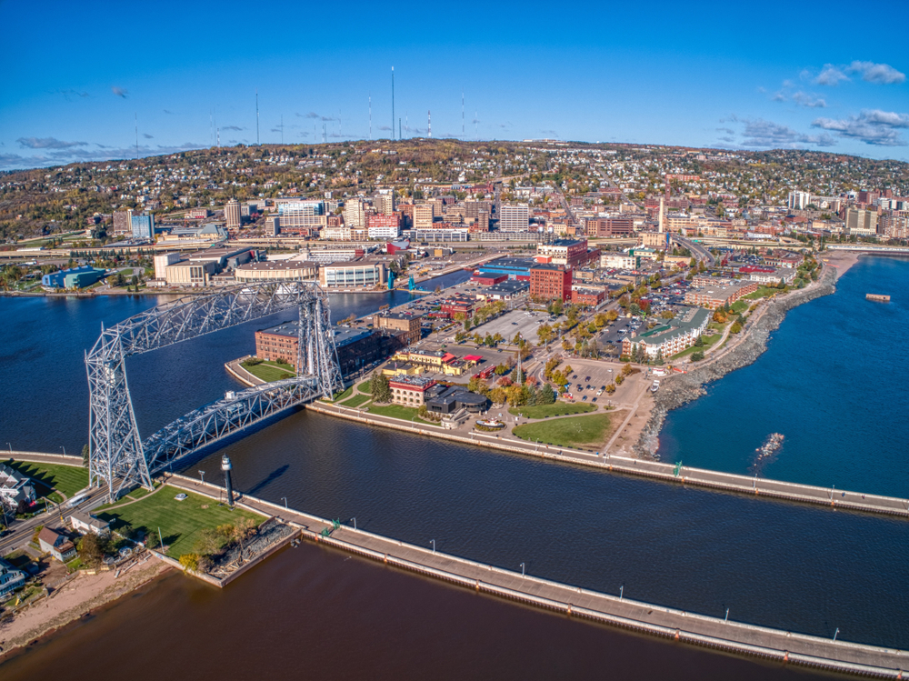An aerial view of Duluth on the edge of the Mississippi River. You can see a large bridge, buildings along the water, and buildings in the distance. The sky is blue with scattered clouds.