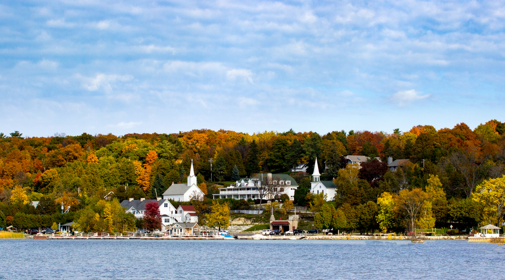 A cute Wisconsin small town being viewed from a lake. On the shore you can see a boat marina. You can also see two white churches with tall steeples, a large Victorian inn, and other buildings. The town is full of trees with red, yellow, orange, and green leaves.