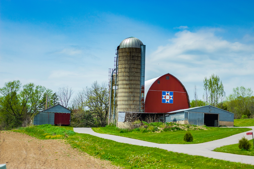 An old barn in Wisconsin. It is painted red and there is a classic style Hex Sign on the side of it. The Hex Sign looks like the patch of a quilt in a sort of star pattern. it is red white and blue. There is also an old silo, and two metal buildings. The barn is surrounded by trees and grass.