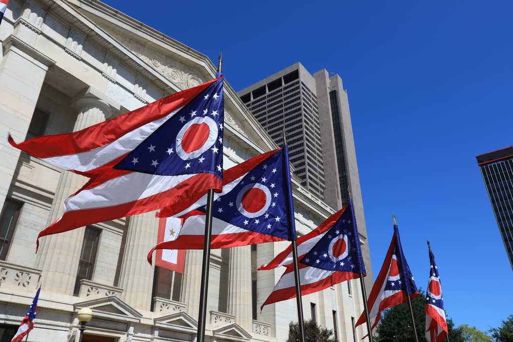 Looking up at four Ohio state flags flying in front of a government building. You can also see a few high rises. The Ohio state flag has a triangle cut out from the middle of it form the the bottom, has red and white stripes, and a blue triangle with white stars and a white O with a red center.