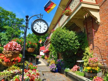 Looking down a sidewalk in the German Village of Columbus Ohio. The houses are surrounded by flower pots with flowers in several different colors. There is a clock hanging on a wrought iron shepherds hook. The buildings are brick with terraces that have German flags hanging from them. One of the best Ohio day trips.