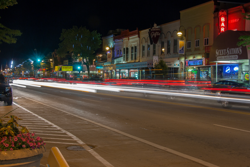 The main street of the Wisconsin Dells at night. The street lights are on, buildings are lit up, and there are cars parked. There are also red and white light streaks going down the road from where cars drove through the picture.