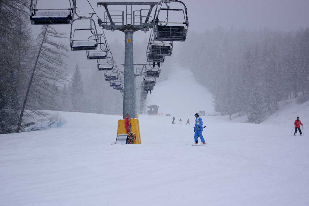 A chairlift on a ski slope during a heavy snowstorm. You can see people skiing, milling around, and riding the chairlift. The sky is a cloudy gray and you can see snow falling. There are trees with no leaves and pine trees. One of the best Michigan ski resorts.