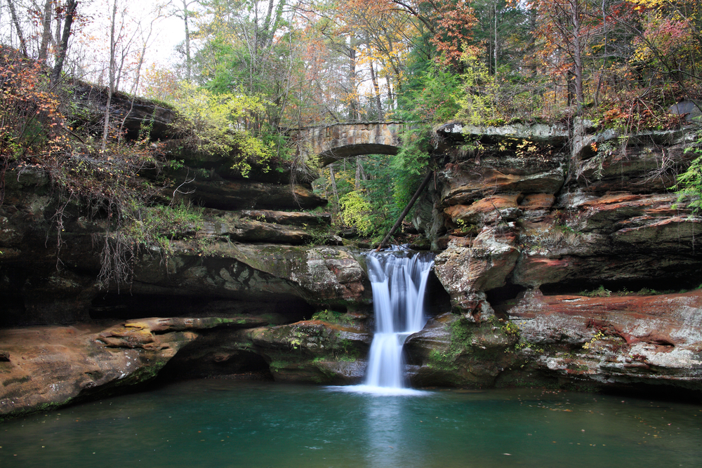 A waterfall cascading over dark stone into a pool of blue water. The rock formation is surround by trees and in the distance you can see a stone bridge that goes over the waterfall. The trees have green, yellow, and orange leaves. One of the best Ohio day trips.