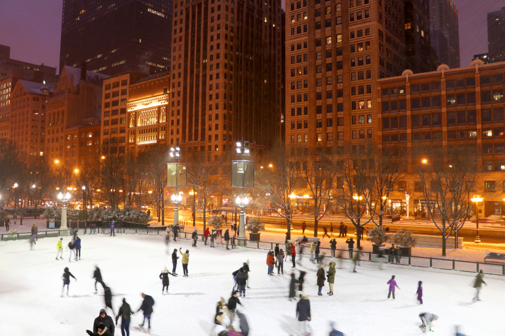 People ice skating at night in a park in Chicago. The buildings are all lit up and the street lights are on. The park is all lit up with large stadium style lights. One of the best things to do during Christmas in Chicago.