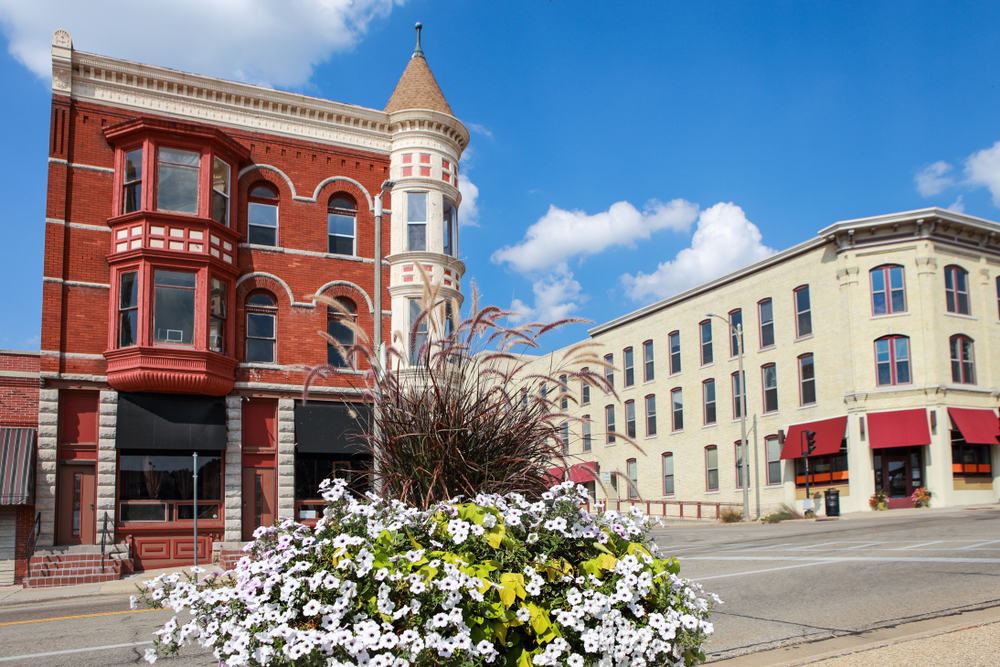 A Main Street in a small town. The buildings are all Victorian style buildings. They are made of red brick or painted a cream color. There is a large flower post with white flowers, tall fuzzy grass, and a bright green plant.