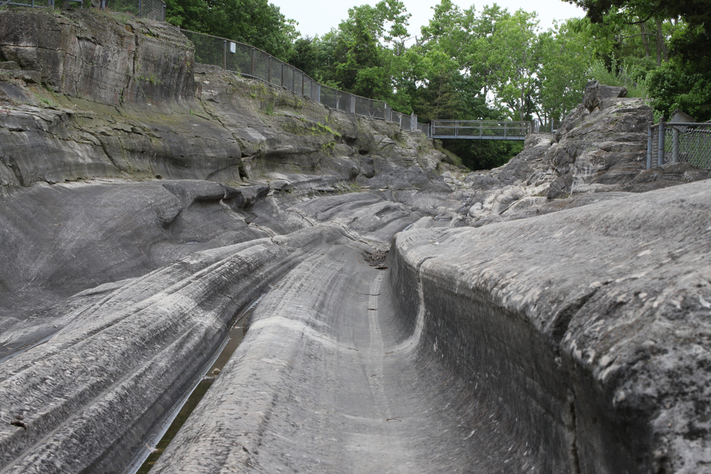 Looking down the path of the Kelleys Island Glacial Grooves. They are smoothed out rock grooves in a dark grey rock. The grooves all fluctuate in depth and shape. In the distance you can see a metal bridge with trees behind it crossing the grooves. One of the best Ohio day trips.