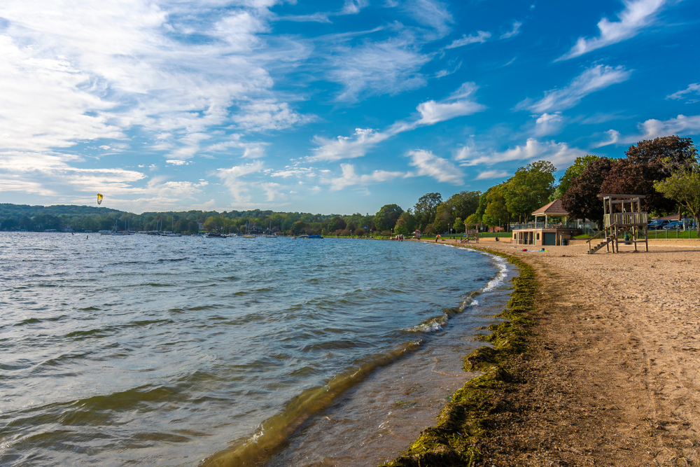 Looking down the sandy shore of a Lake in Wisconsin. On the shore you can see a lifeguard stand, a brick building, and people walking on the beach.