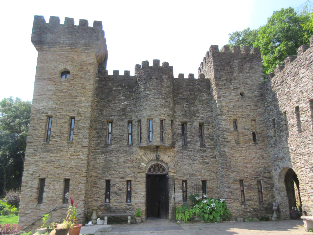 The exterior of an eclectically designed stone castle in Ohio. There are several towers in different shapes, long narrow windows, and doorways with arched entries. Behind the castle you can see some trees. One of the best Ohio day trips.