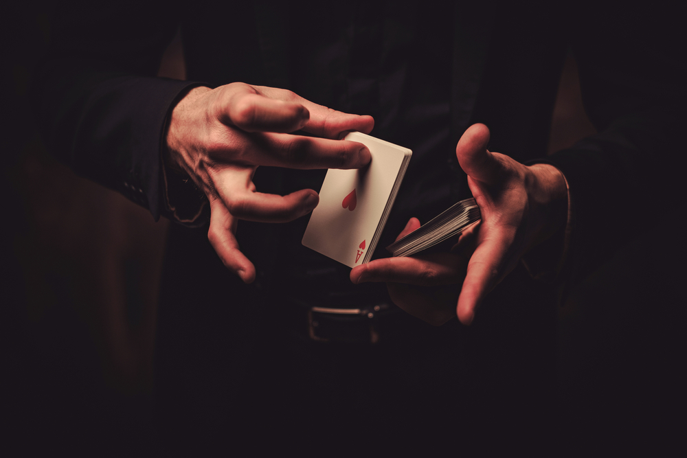 A person's hands holding a deck of cards like they are going to perform a magic trick. The Ace of Hearts can be seen upside down in their hand. They are wearing all black and the background is black.