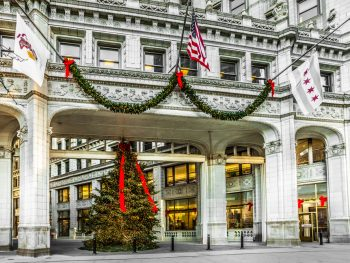 A large ornate shopping district entrance of the Magnificent Mile in Chicago. In the middle of the ornate arch way entrance is a large Christmas tree lit up with a big red bow on it. There is also a sway of greenery with red bows and lights hanging on the archway.