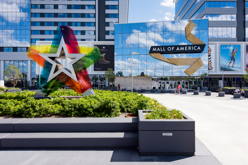 The exterior entrance to the Mall of America. IT is a large multi level building with windows that are reflecting the sky. In a area with small shrubs there is a large rainbow colored translucent star. One of the best things to do in Minnesota.