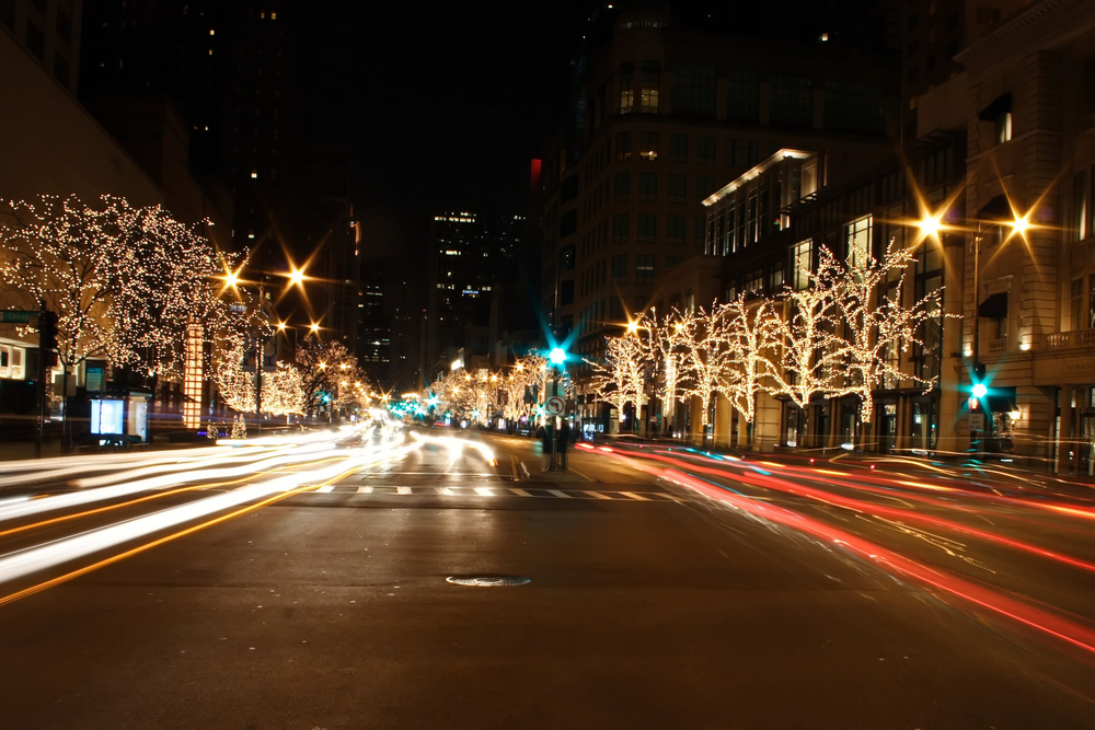 A main street in Chicago in the winter. There are trees lining the street and they are covered in twinkle lights that are all lit up. It is night time and on the street you can see light streaks from cars passing by.