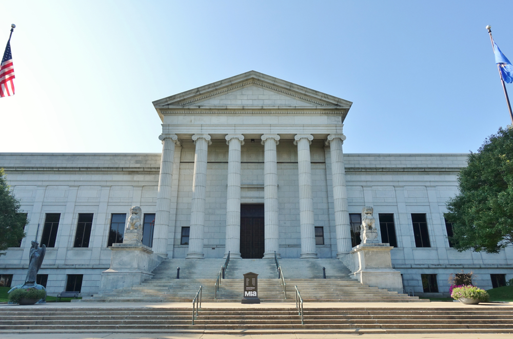 The front entrance to the Minneapolis Institute of Art. It is a large Roman style building made of stone with tall columns on the front. It has steps leading to the front door and a pair of carved stone lions on either side.
