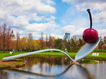 A large sculpture of a spoon with a cherry perched on top of it. The spoon is resting on the shore and crosses to the middle of a small lake. Around it is a grassy area with benches and trees in the distance with little to no leaves. Behind the trees you can see a city skyline. One of the best things to do in Minnesota.