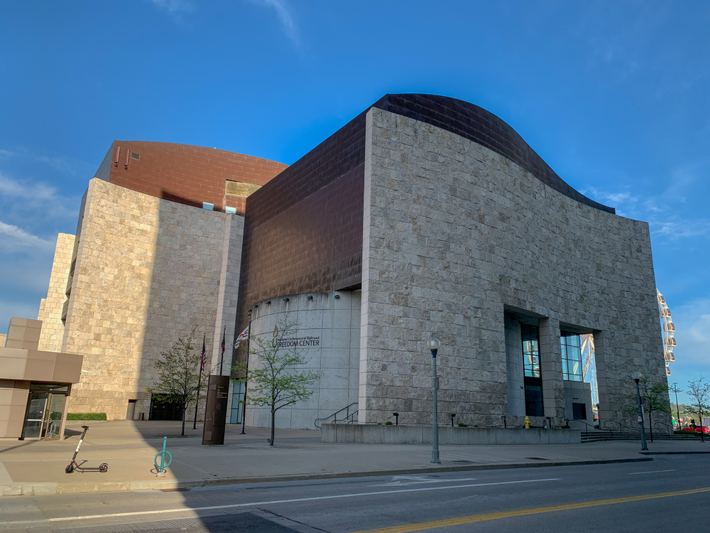 The exterior of the National Underground Railroad Freedom center. It is a stone building with different angles and a dark brick roof and siding. Behind it you can see a small ferris wheel and in front of it is a courtyard with small trees.