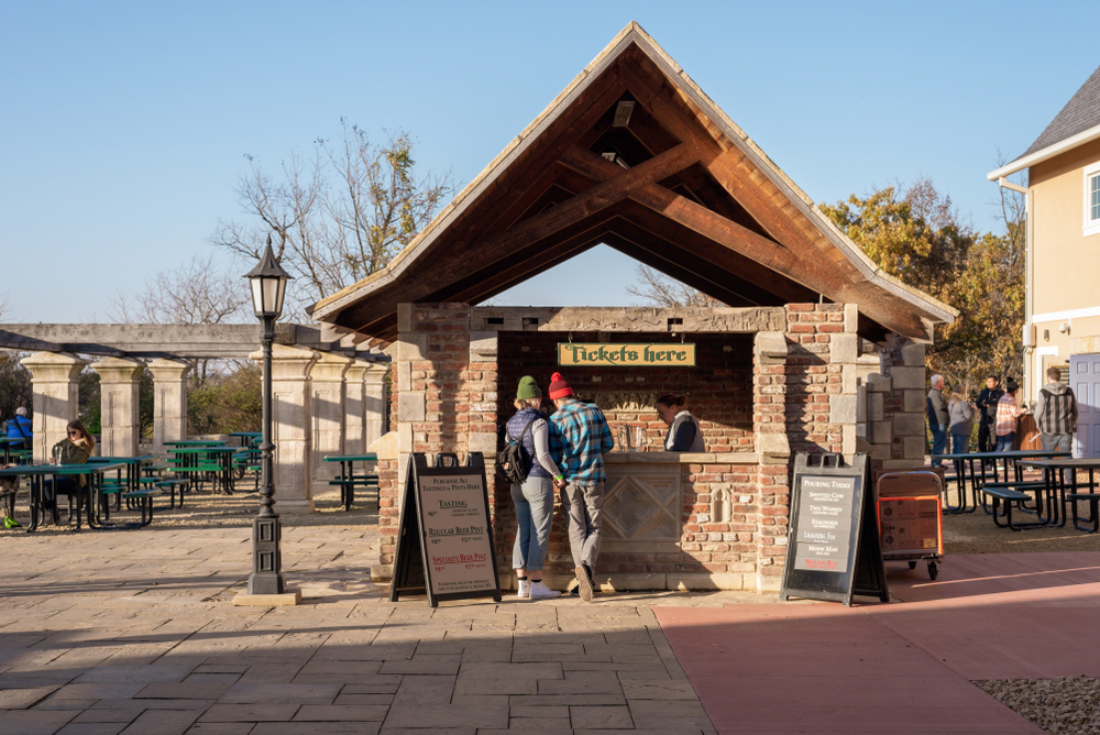 People standing in front of a brick ticket counter to get into one of New Glarus' beer gardens. You can see other people walking around and green outdoor tables.
