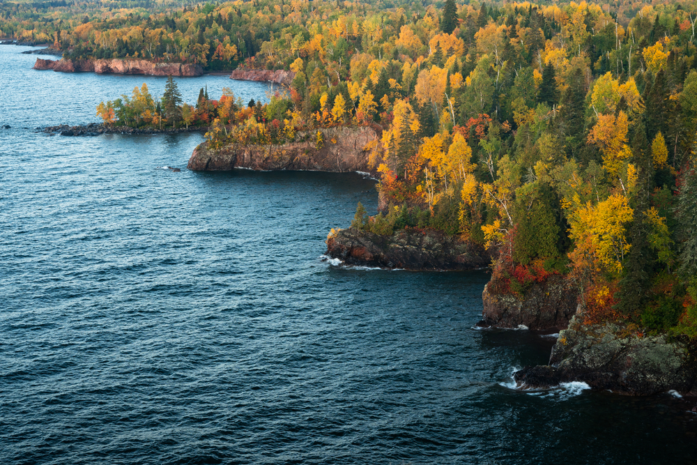 A rocky shore line along Lake Superior, one of the best things to do in Minnesota. On the rocky cliffs there are trees growing. They have red, yellow, orange, and green leaves.