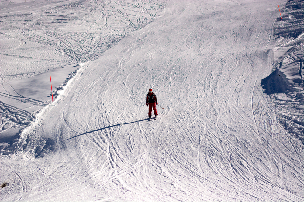 A person in a red snowsuit skiing down a ski slope. They are the only person on the wide path down the ski slope. You can see tracks from where other people have skied down the slope.