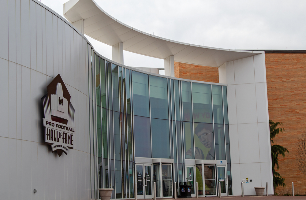 The exterior of the Pro Football Hall Of Fame. It is a partially brick building with a large entry made of floor to ceiling windows inside a white stone portion of the building. You can see a sign for the museum and pictures hanging in the building of different football players.