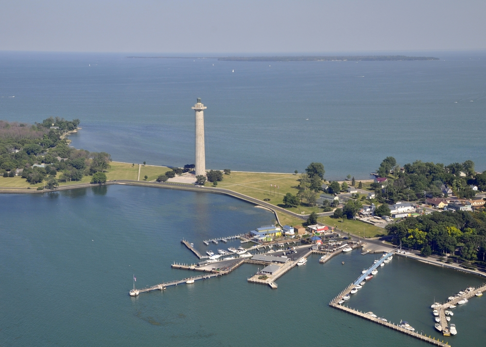An aerial view of Put-in-Bay on South Bass Island. You can see a large stone tower memorial, grassy areas with trees, a few buildings, and a boat marina. The island is surrounded by water in Lake Erie.