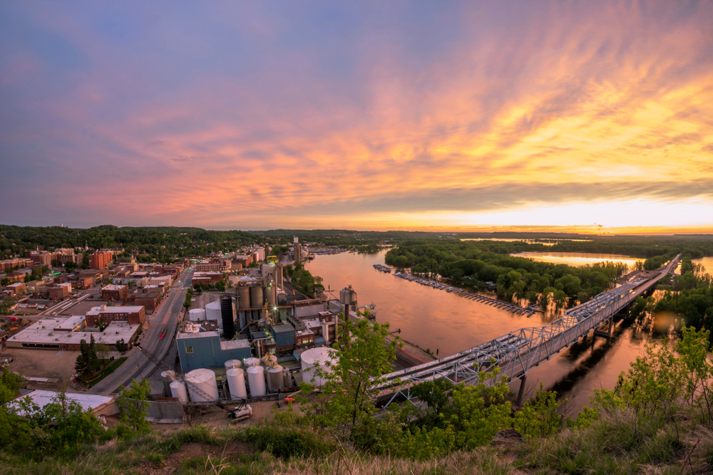 An aerial view of Downtown Red Wing. You can see a bridge crossing the river, factories, and other buildings. In the distance there are trees and there are trees along the river. It is sunset and the sky is orange, yellow, pink, and blue.