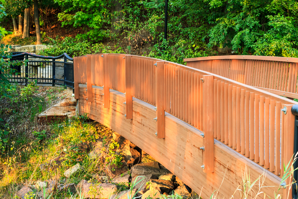 A wooden bridge crossing over a river bed with rocks on the side. Past the bridge you can see a walk way with a black iron railing. The bridge and walkway are surrounded by trees. Dells WI