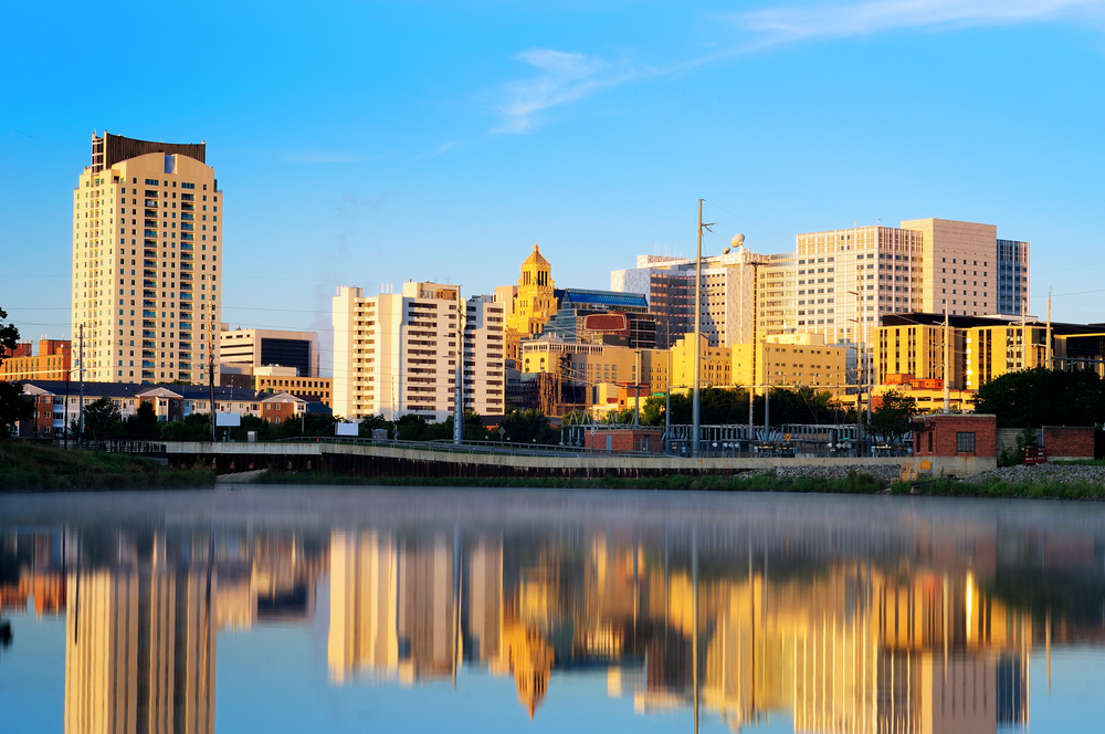 The view of the Rochester skyline from the water. There are lots of buildings at all different heights. You can see the buildings reflecting into the river.