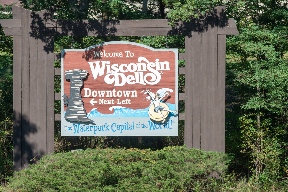 A sign welcoming you to the Wisconsin Dells. It has a rock formation on it as well as a child in an innertube riding a wave. The sign is on a big wooden frame and is surrounded by trees and shrubs.