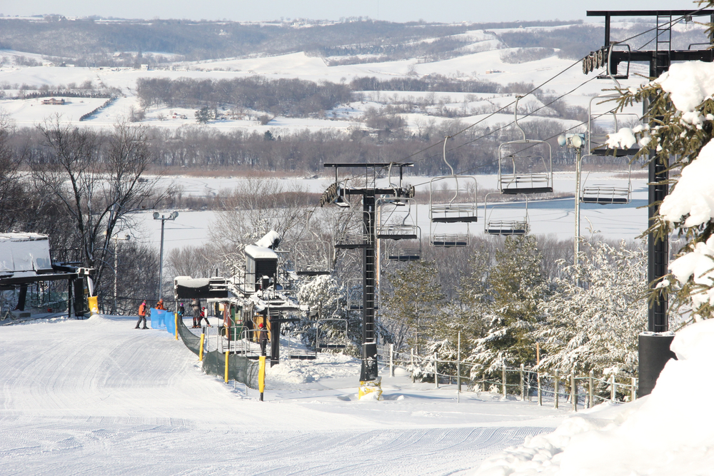 An area of ski slopes in Wisconsin. The mountain is covered in snow and you can see snowy hills in the distance. There are a few people lined up to get on a ski lift.