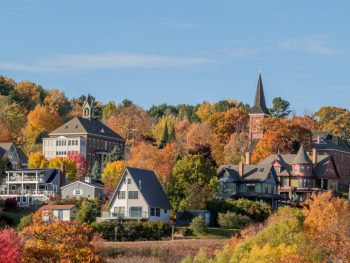 The skyline of one of the cutest small towns in Wisconsin. You can see old homes, buildings, and a church steeple peaking through the tops of trees. The trees have red, yellow, orange, and green leaves on them.