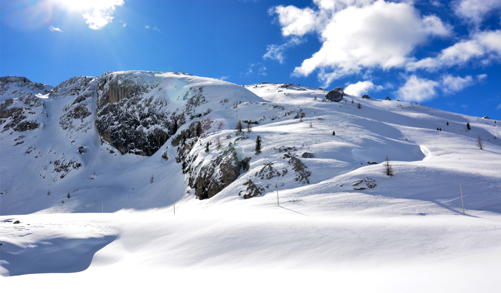 The view of a mountain side covered in snow. You can see a barrier that creates a path for people to ski. The mountain and ground is covered in a thick layer of snow. It is sunny with a bright blue sky and some clouds.