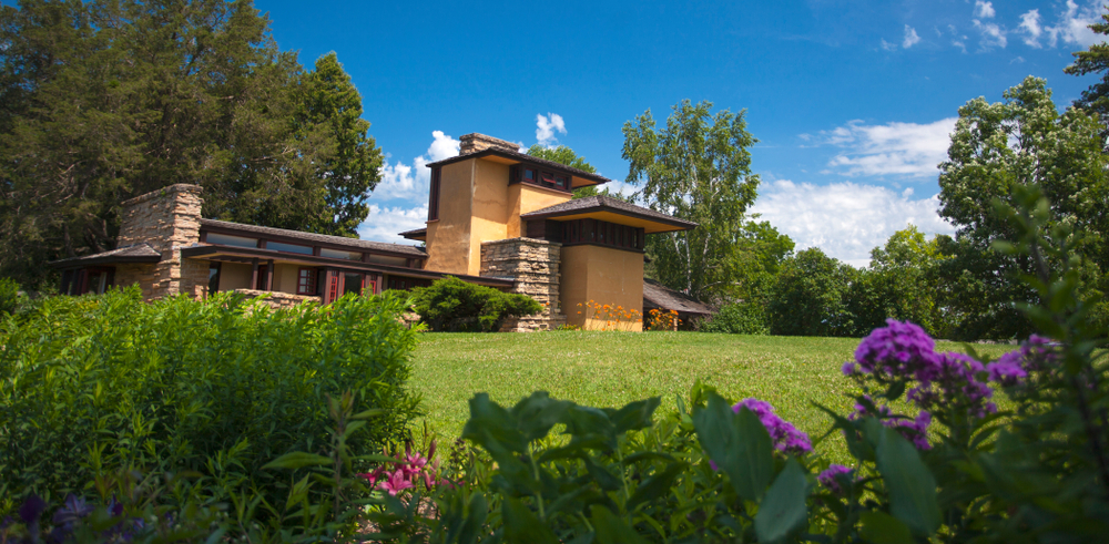 A Frank Lloyd Wright designed home that features yellow stucco, tan stones, and a brown roof. It is very angular and there is a large green lawn in front of it. You can also see shrubs with purple and pink flowers and trees.