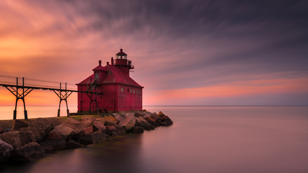 A red lighthouse on the end of a stone pier in the middle of a lake. There are power lines leading to the lighthouse. The water surface is calm and the sun is setting so the sky is orange, yellow, pink, and purple.