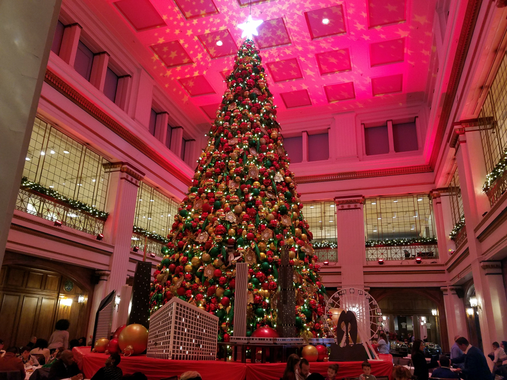A large elaborately decorated Christmas tree on a pedestal in the middle of a large room. The room is colored with redish pink lights, there are windows high on the wall, and people are sitting at tables around the tree.