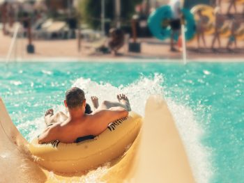 Male riding yellow tube down yellow waterslide Things to do in Wisconsin