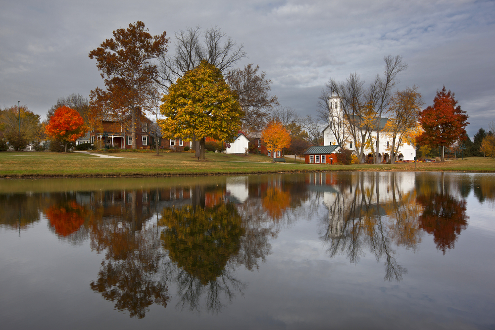 Looking across a pond at a brick farmhouse that has a few smaller buildings around it. Near the shore of the pond is a large white church with a steeple. The area is grassy and there are trees with red, yellow, and orange leaves on them.
