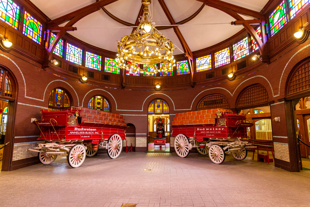 The inside of the Anheuser-Busch Brewery with wagons, a chandelier, and stained glass.