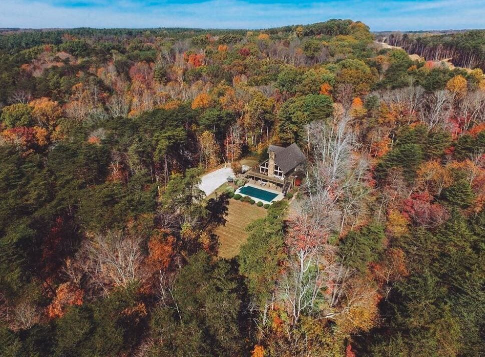Aerial view of Cabin in Hocking Hills completely surrounded by brilliant autumnal trees. Blue rectangular pool in front of house. Cabin has large windows and wooden deck.