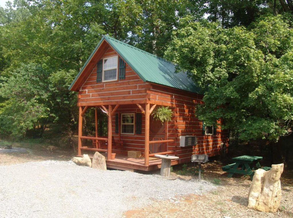 Brown wooden cabin with green meatal roof. Front porch with wooden beams. Gravel driveway in forefront. Midwest cabin.