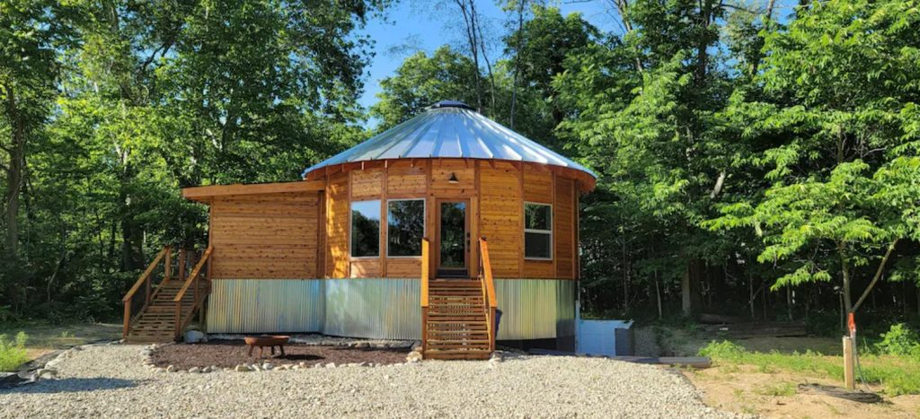 Round wooden yurt with silver metal roof. Wooden staircase to glass front door, windows on either side. Cabins in the Midwest