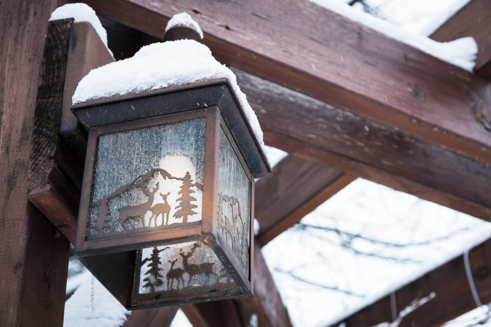 Bronze lantern with animal cutouts and white candle inside, has snow on top of it, handing from dark wood beams.