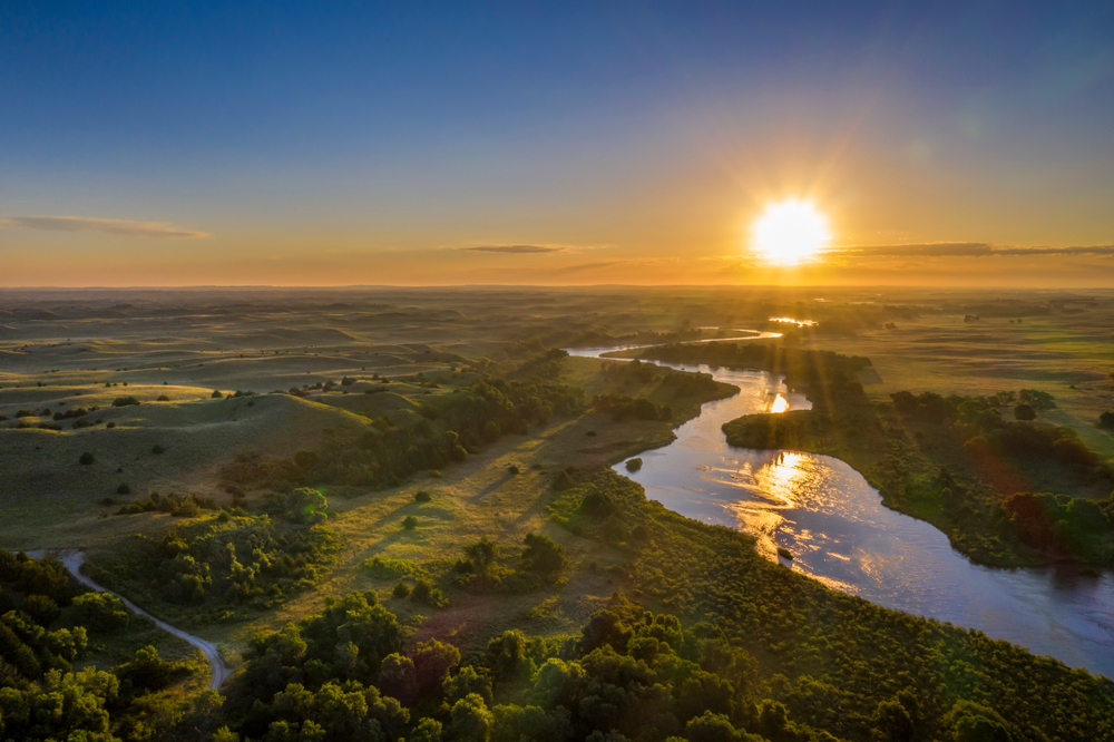 Yellow sun setting over green plains with river flowing through middle.