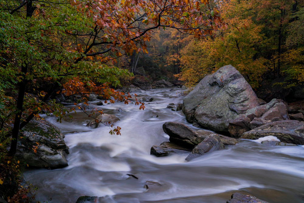 Waterfall flowing through rocks with large boulder on right with autumn leaves in background. Cabins in Ohio.