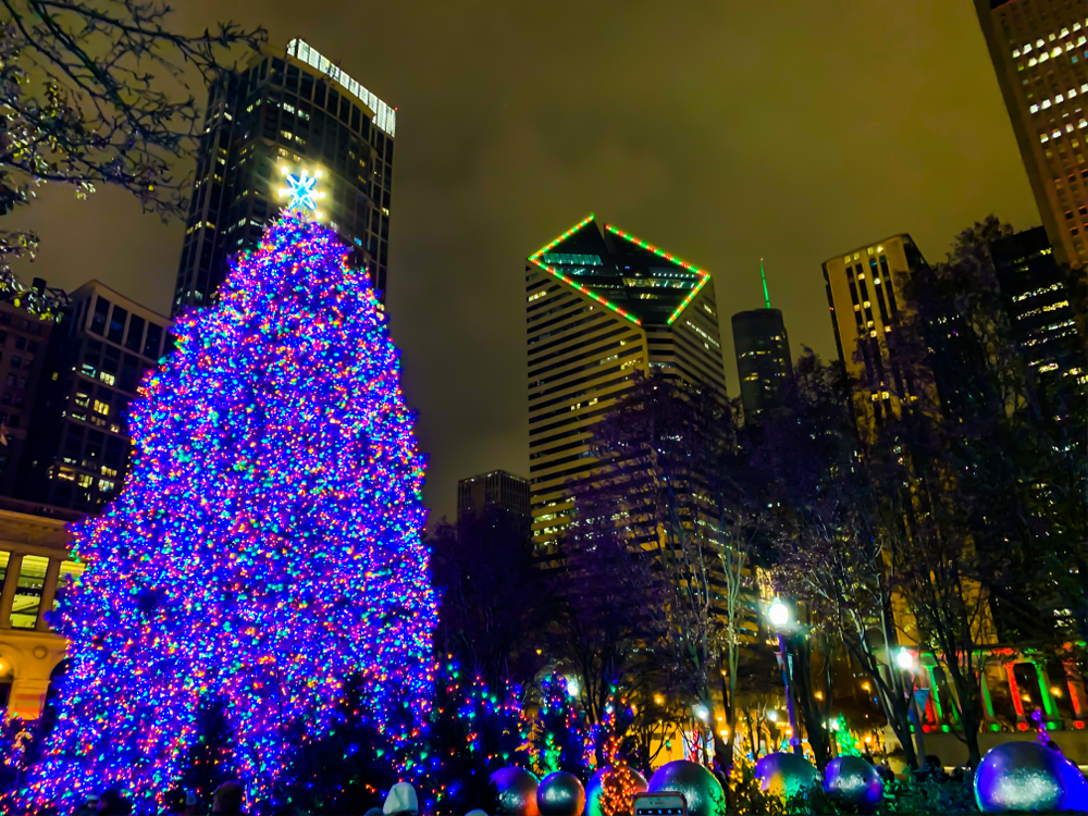 The Christmas tree in Millennium Park with bright, purple lights and skyscrapers in the background at night.
