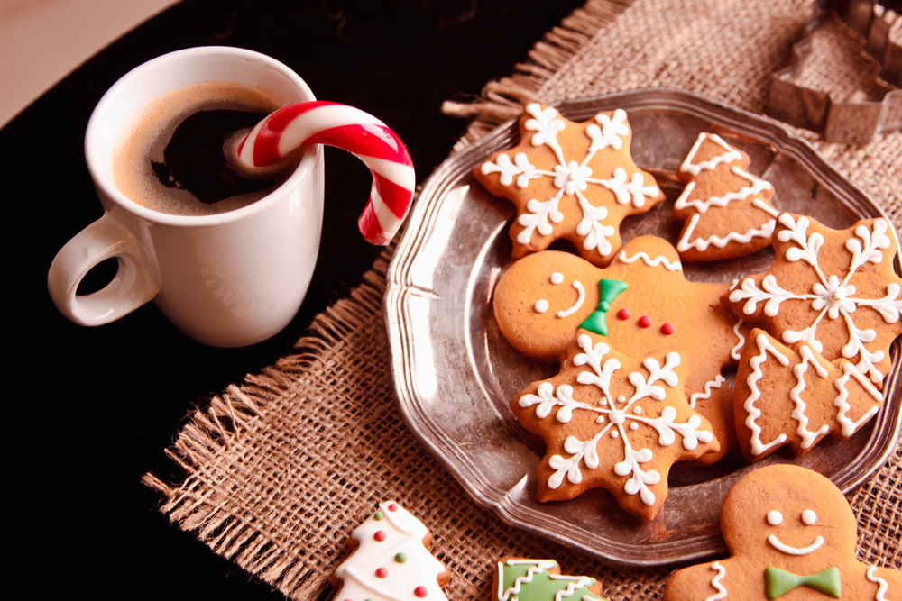 A plate of Christmas cookies on a table next to a mug of hot cocoa with a candy cane.