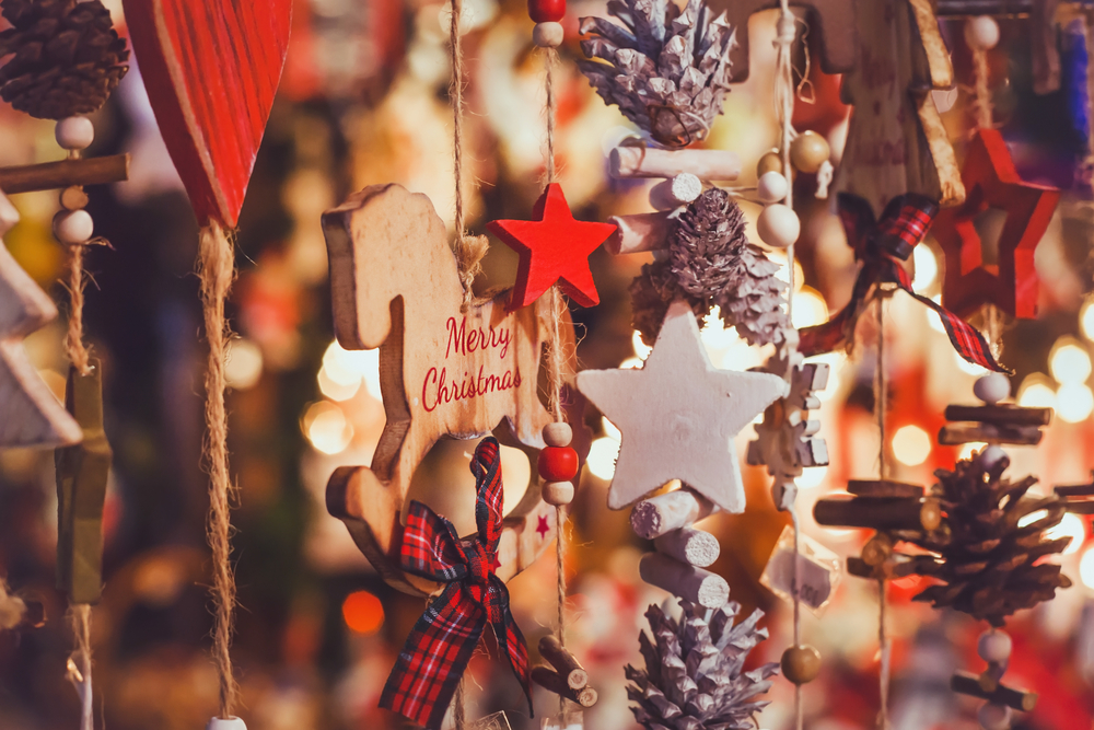 Handmade Christmas decorations made from wooden stars and pine cones at a market.