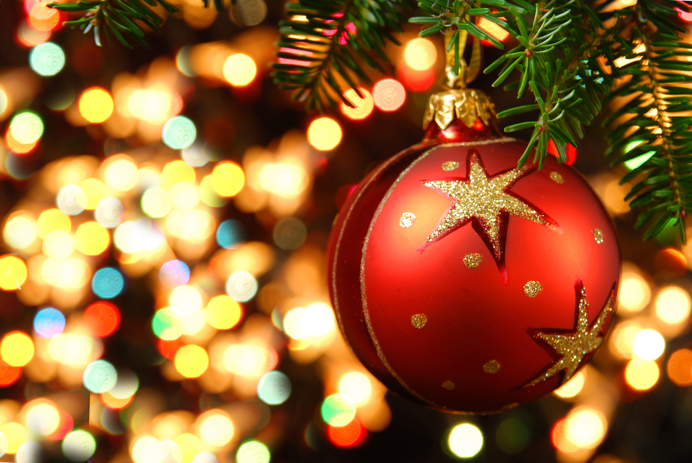 Close-up of a red and gold Christmas tree ornament with pretty lights in the background.