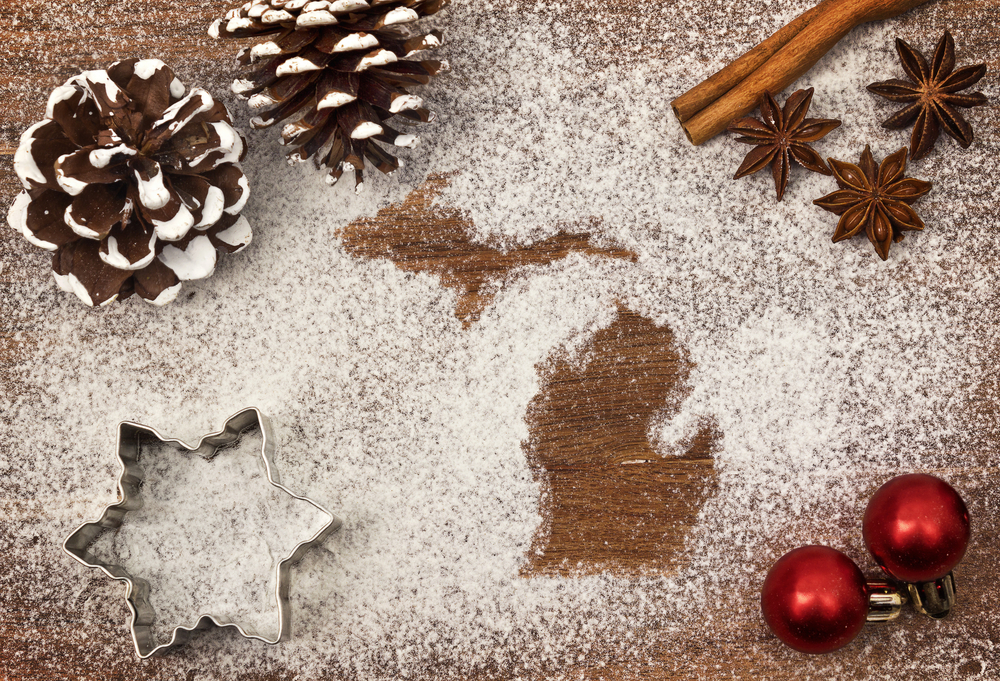 two pinecones, red ornaments, a star cookie cutter surround imprints of state of Michigan in powdered sugar. Christmas in Michigan.